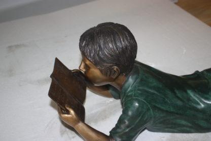 "boy laying reading book bronze Statue -  Size: 24""L x 10""W x 11""H."